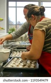 BIELEFELD, NORTH RHIJN WESTFALEN / GERMANY – NOVEMBER 6 2015: Two young women backing cookies in kitchen by Dr. Oetker World.