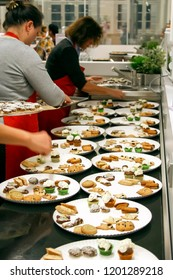BIELEFELD, NORTH RHIJN WESTFALEN / GERMANY – NOVEMBER 6 2015: People divide fresh baked cookies on several white plates in kitchen by Dr. Oetker World.