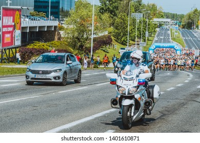 Bielsko-Biala, silesian voivodesphip, Poland - 05.19.2019: Policeman on the motorbike and people running main street during Fiat Run in 10 km Bielsko-Biala