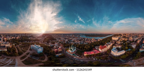 A big 360 degrees panorama of the city of Kiev on Podol at sunset. A modern metropolis in the center of Europe against the backdrop of sunset sky from a bird's eye view. Aerial view. Panorama of the