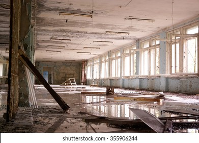 big abandoned hall with big broken windows, white  on the floor and puddles.