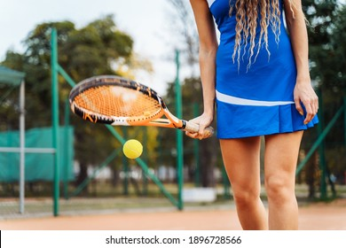 Big achievements and victories come by taking small steps. Training endurance and coordination by hitting a tennis ball with a racket. Sports activities on a clay tennis court.