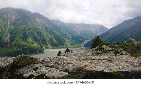 Big Almaty lake located in the mountains of Kazakhstan. It offers views of green grass, flowers, lake, rocks, large mountains and the sky in the clouds. Mountain lake with blue water.