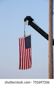 Big American flag hanging from a crane.