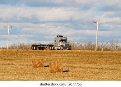 Big American truck on country side road through harvest fields