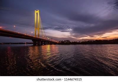 big arc bridge across river sunset