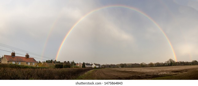A big arching rainbow over a small countryside Suffolk village