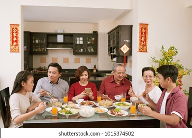 Big Asian family enjoying big dinner for New Year celebration. Scrolls wishing luck and wealth in the background