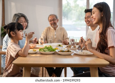 Big Asian happy family spend time having lunch on dinner table together. little kid daughter enjoy eating food with father, mother and grandparents. Multi-Generation relationship and activity in house - Shutterstock ID 1994199293