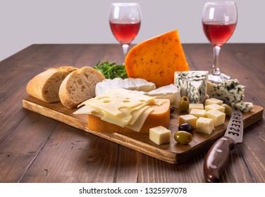 A big assortment of different kind of cheeses on a wooden table.