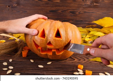 A big autumn halloween pumpkin with leaves on a wooden background. Halloween concept