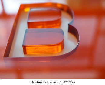 "Big ""B"" letter shape groove engraved on red orange thick transparent acrylic glass, perspective shot with sunlight reflection from window"