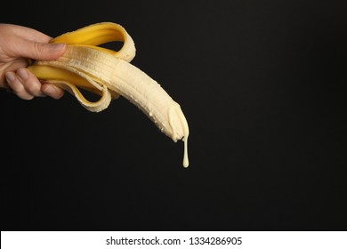 Big banana and drops of condensed milk. Concept of sex, man ejaculation. Sperm and orgasm.