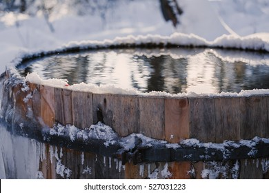 Big barrel with clean cold water outdoors in forest covered with snow. Winter swimming concept