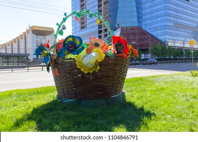 Big basket with artificial flowers on the city street. Urban