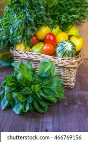 The big basket with basil, arugula and spinach on a wooden table. In the foreground - vegetables, tomatoes and bush pumpkins