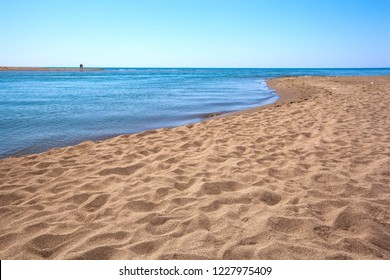 Big beach with yellow sand on the shore at the confluence of the Buna River in the Adriatic Sea and Bojana Island is seen beyond the river. Beach on Ada Bojana, Ulcinj, Montenegro.