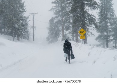 Big Bear, CA. Winter snow storms had hit hard in area on January 23, 2017. Residents or visitors had to travel on foot. Man holding gallon of water and foods bag.  Natural disaster concept.