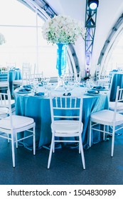 Big beautiful decorated restaurant at the wedding, wedding in blue and white colors, orchids flowers in vases with blue water
