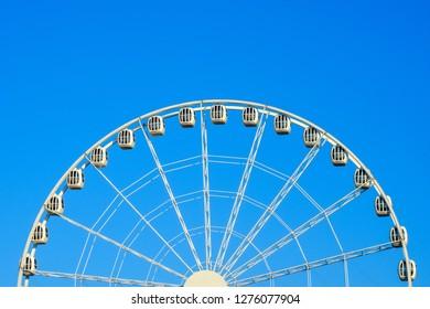 Big beautiful ferris wheel in the park against the blue sky.