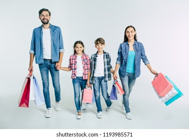 Big beautiful happy and excited family walking together after shopping in the mall with purchases in hands isolated on white