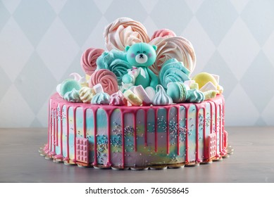 Big beautiful kids cake decorated with turquoise Teddy bear and colorful meringues and marshmallows. The concept of festive desserts for the birthday children