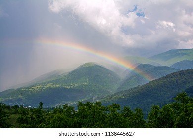 A big beautiful rainbow after a rain on a background of mountains, forests and mist in Dilijan, Armenia