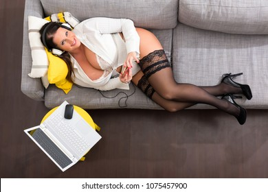 A big and beautiful woman relaxing in lingerie on the Sofa.