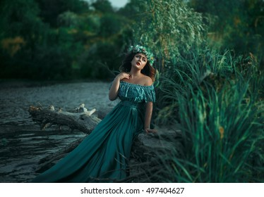 A big beautiful woman. The river witch casts a spell on the water. Green long dress, a wreath of herbs, a fabulous image.Fabulous image. Fashionable toning. Creative color.
