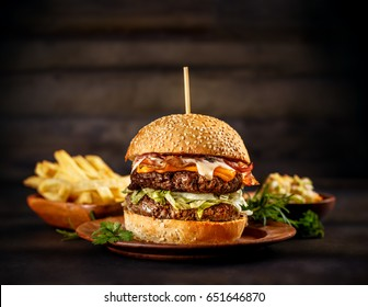 Big beef burger with melted cheese and bacon on wooden plate