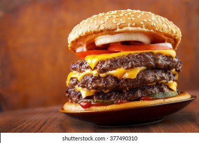 Big beef burger with three patties and cheese on plate , wood background