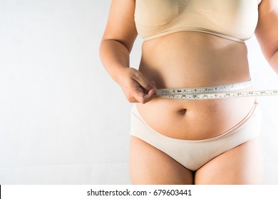 big belly of a fat man and measuring tape isolated on white