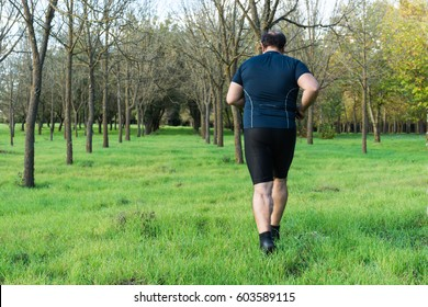 Big belly man jogging , exercising, doing cardio in the park , slightly overweight, loosing weight. On a lawn of green grass between trees without leaves.
