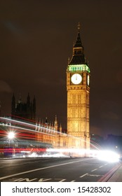 Big Ben with a double-decker bus passing by at midnight;  