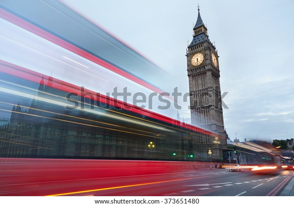 Big Ben in the early morning and red bus passing in London, natural colors