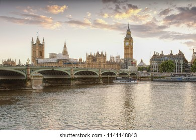 Big Ben, famous tower clock in London,Uk, photographed during golden hour on summer evening from south bank of Thames river.Sunset over Thames.Crowd of people on Westminster Bridge.