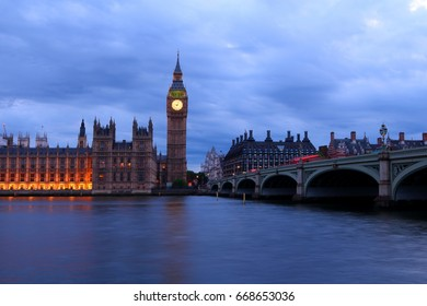 Big Ben and the House of Parliament of UK viewed from the opposite side of River Thames, along with Westminster Bridge, at night