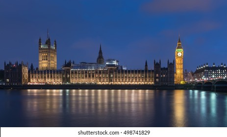 Big Ben -- Houses of Parliament, the Palace of Westminster, with half-mast flag in blue sky taken across the river