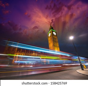Big Ben with the Houses of Parliament and a red double-decker bus passing at dusk.