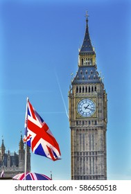 Big Ben Tower British Flag Houses of Parliament Westminster London England.  Named after the Bell in the Tower. Has kept exact time since 1859.