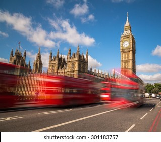 Big Ben in Westminster with red London Buses going past during the day. There is space for text in the image