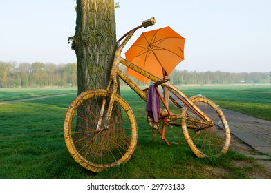A big bicycle with an orange umbrella