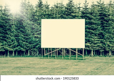 Big billboard sign surrounded by trees