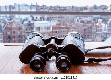 Big black binoculars lying on the table against the window overlooking Amsterdam.
