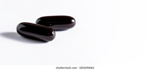 Big black soft gel medical capsules  on white background. Long banner format. Health care and immunity support concept.