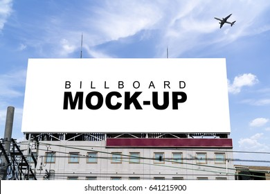 A big blank Billboard mockup for advertisement on the top of modern office building with blue sky background, with clipping path