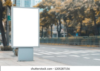 big blank billboard white LED screen vertical outstanding in the city on pathway side the road traffic for display advertisement text template promotion new brand at outdoor with green tree.