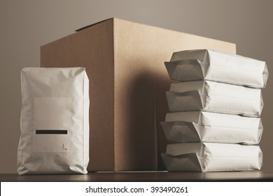 Big blank bulky sealed package with product presented in front of carton craft box and column of other packages. Ready for shipping, delivery and sale. Small business artisan concept.