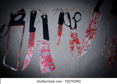 Big bloody knife and kitchen items hanging on the wall in blood.Halloween.