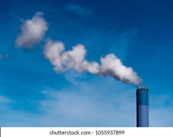 Big blue chimney gives white steam in the blue sky